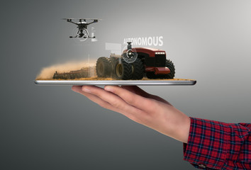 Wall Mural - Farmer holding a tablet with autonomous tractor and drone. Smart farming