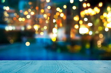 blur light of bar or pub beside blue water swimming pool summer party at night with top of wood table background