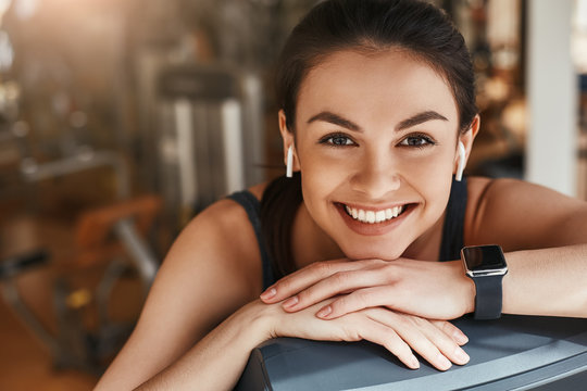 Always in good mood! Portrait of cute and cheerful woman with smart watch on her hand looking at camera with toothy smile while taking a rest at gym.