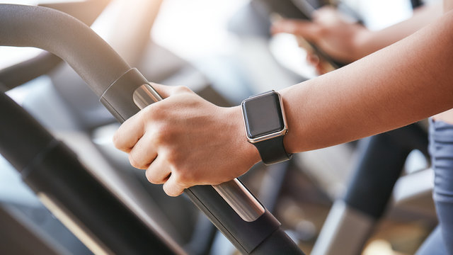 Smart technologies. Close-up photo of smart watch on woman hand holding the handle of cardio machine in gym
