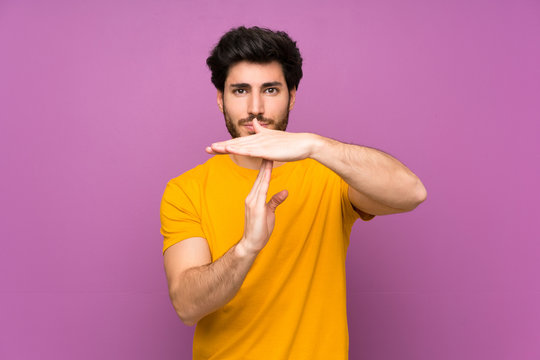 Handsome over isolated purple wall making time out gesture