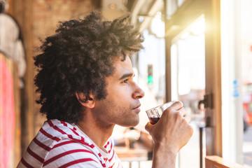 Thoughtful mixed race man drinking soda at cafe bar