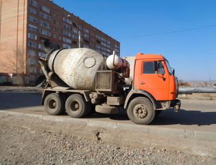 Concrete mixer on the street. Construction engineering. Orange truck. Blue sky. Ust-Kamenogorsk (Kazakhstan).