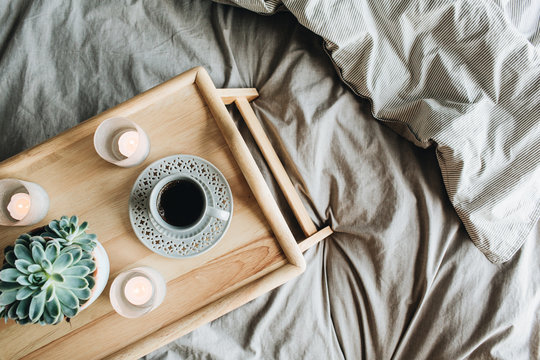 Morning breakfast with coffee in bed. Flat lay, top view lifestyle still life composition. Wooden tray and grey linen.
