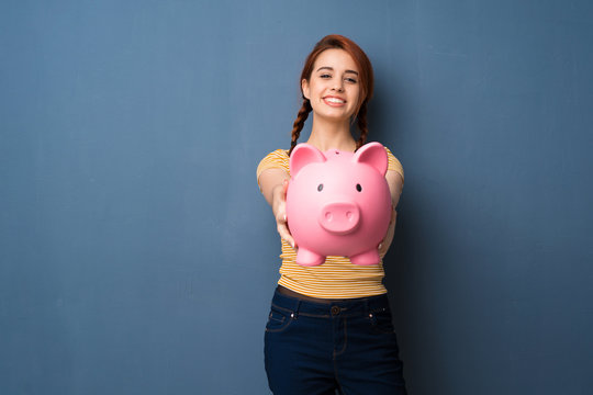 Young redhead woman over blue background holding a piggybank