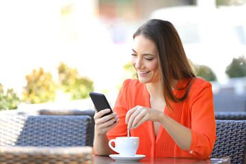 Happy woman using phone stirring coffee in a bar