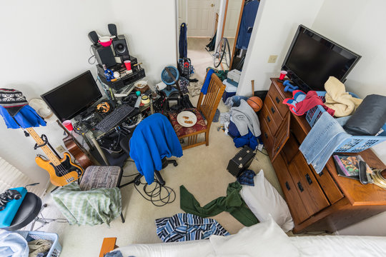 Very messy, cluttered suburban teenage boys bedroom with piles of clothes, music and sports equipment.