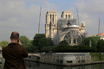 A man takes pictures of Notre-Dame Cathedral after a massive fire devastated large parts of the gothic structure in Paris