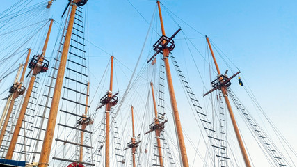 High wooden masts and historical ship rigging against blue sky
