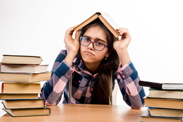 Exams at school. Education. Tired eyes from reading. Printed books, study at school. Library. Girl with books. student is sitting at the table with books. Learning fatigue.