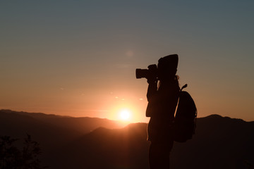 The photographer's silhouette with his camera on a sunset