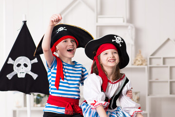 Boy and girl in pirate costumes, play enthusiastically. On their heads pirate hats with skull and bones.