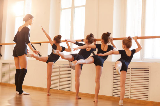 Back view portrait of group of little girls stretching standing by bar in ballet class, copy space