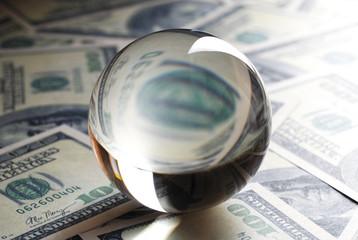Glass ball on dollars. Dollar banknotes.