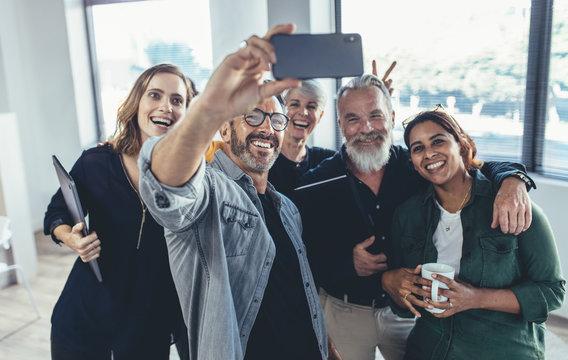 Cheerful people in the office taking selfie
