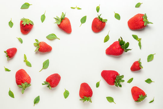 Colorful pattern made of strawberries and green leaves. Minimal summer concept.