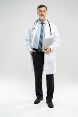 full body picture of a mature doctor holding a notepad, on white background.