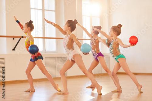 Team of little girls practicing rhythmic gymnastics in class