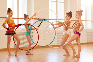 Team of little girls practicing rhythmic gymnastics with hoops, copy space