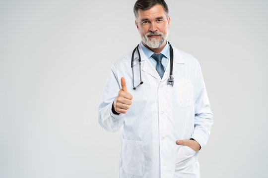 Happy smiling doctor with thumbs up gesture, isolated on white background.