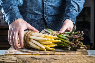 cropped of man holding bunches of green and white tied asparagus.