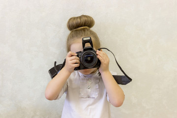A little girl in business clothes holds a reflex camera in her hands in front of her face. The child wants to take a picture. The baby learns to take pictures and studies the complex technique