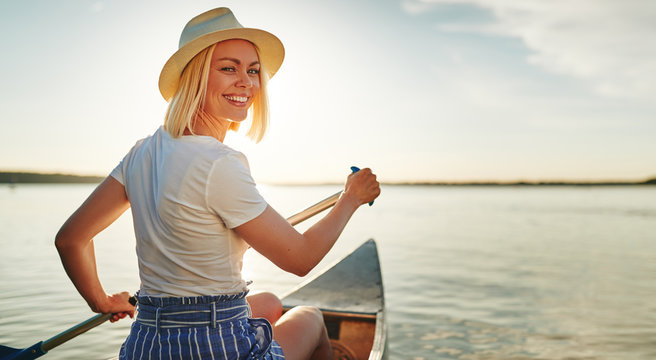 Smiling young woman canoeing on a lake in summer