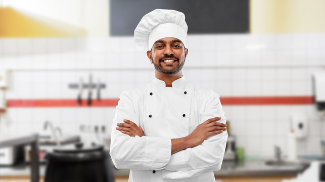 cooking, profession and people concept - happy male indian chef in toque with crossed arms over restaurant kitchen background