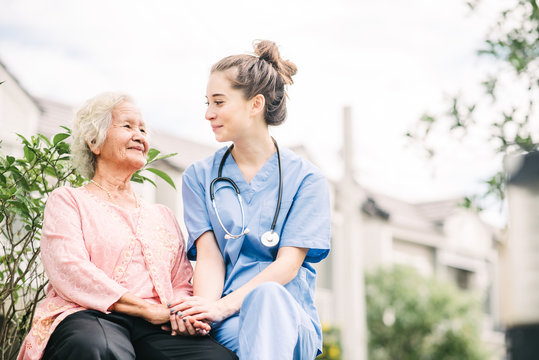 caregiver holding hand of happy elderly woman