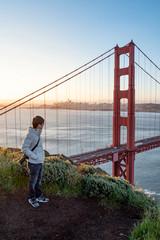 Asian man photographer and tourist enjoy looking at Golden Gate Bridge during sunrise, Iconic bridge and famous landmark of San Francisco, California, USA. Travel photography concept
