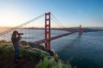 Asian man photographer and tourist enjoy taking photo of Golden Gate Bridge during sunrise, Iconic bridge and famous landmark of San Francisco, California, USA. Travel photography concept