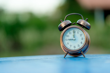 Golden alarm clock picture placed on a blue table, green background Punctual concept With copy space