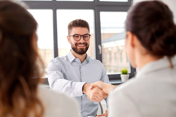new job, hiring and employment concept - team of recruiters having interview with male employee and shaking hands at office