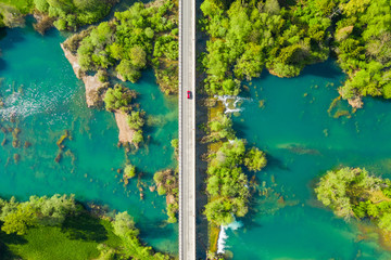 Red car crossing road bridge over Mreznica river in Croatia, overhead shot of countryside landscape, waterfalls and trees in spring Wall mural