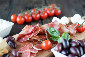 Prosciutto, bread, olives,  mozzarella, salami, basil and cherry tomatoes on  brown wooden board.  Mediterranean kitchen.