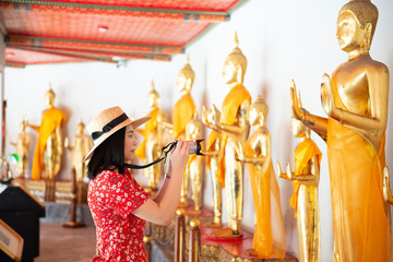 Wall Mural - Young Asian woman is traveling inside Wat Pho in Bangkok, Thailand.