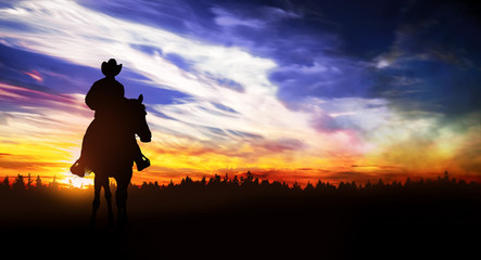 cowboy riding in the hills at sunset Wall mural