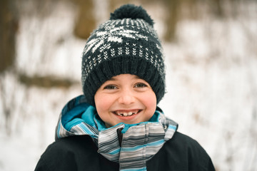 fcaf300caf6c8 Close up of smiling young boy outside in winter wearing clothing.