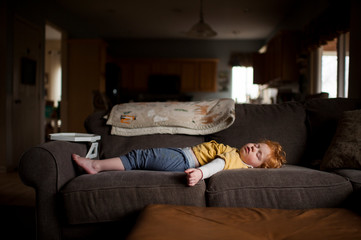 Exhausted little boy asleep on couch at home