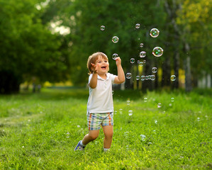 Beautiful 2 year old boy playing in the summer outside in the greenery with soap bubbles