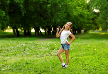 A charming girl in shorts and a t-shirt smiles in the summer against the green in the park