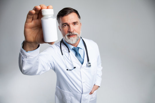 Smiling doctor holding up a bottle of tablets or pills with a blank white label for treatment of an illness or injury.