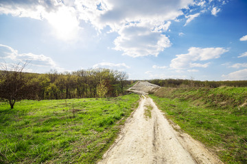Fototapete - Beautiful view of road in the field and green forest and blue cloudy sky and top of the hill. Spring rural landscape.