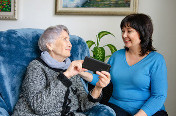 Cheerful female caregiver teaching an elderly woman how to use a smartphone