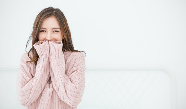 Portrait of young beautiful asian woman in bedroom. Smile happy asian girl hands cover face wear winter cloth. Beauty treatment perfect clear skin japanese makeup  lifestyle concept panoramic banner