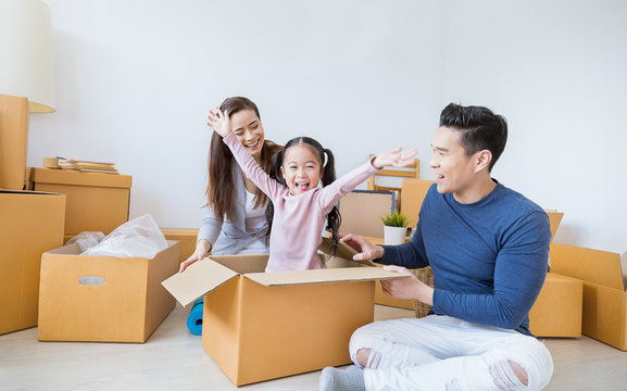 Asian family father mother daughter girl packing cardboard box moving to new house, online marketing e-commerce unpacking stuff delivery. Lifestyle happy asian family together relocation concept.