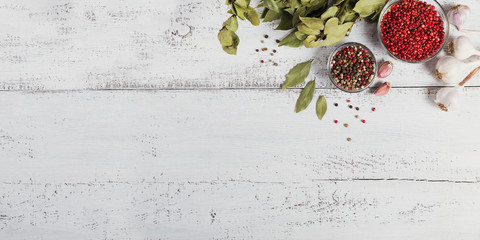 Assorted pepper spices. Pepper mix. Black, red and white peppercorns, dried bay laurel leaves and garlic on white wooden background.