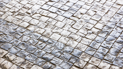 Paving stones in the old European city. Background from paving stones. Stone road in the old town....