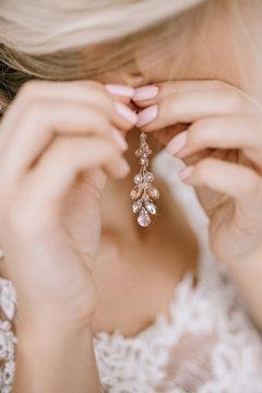Elegant blonde bride putting on earrings closeup, preparing for wedding