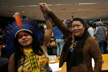 Congresswoman Joenia Wapichana and Indigenous Leader Sonia Guajajara raise their hands during a meeting with congressmen during the Terra Livre camp, or Free Land camp, at the National Congress in Brasilia